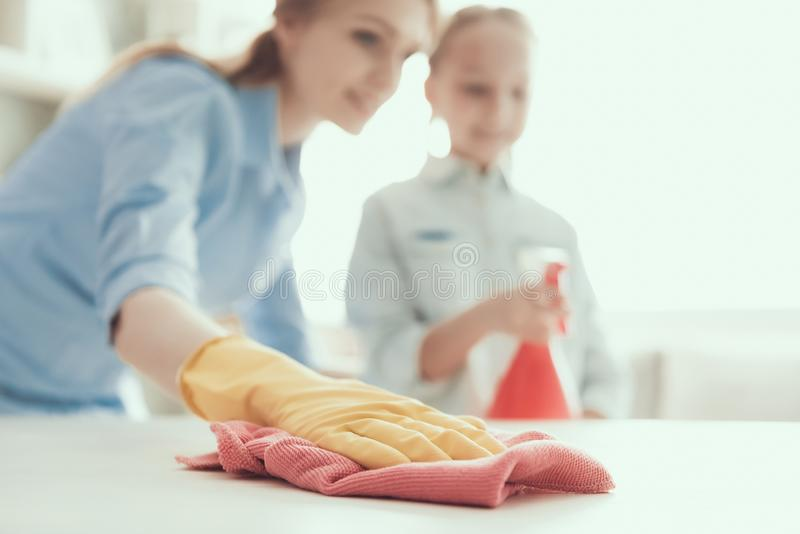 Happy Mother and Dauther Cleaning House Together. Closeup of Young Smiling Mom wearing Protective Gloves Wiping Desk with Sponge while Little Girl holding stock images