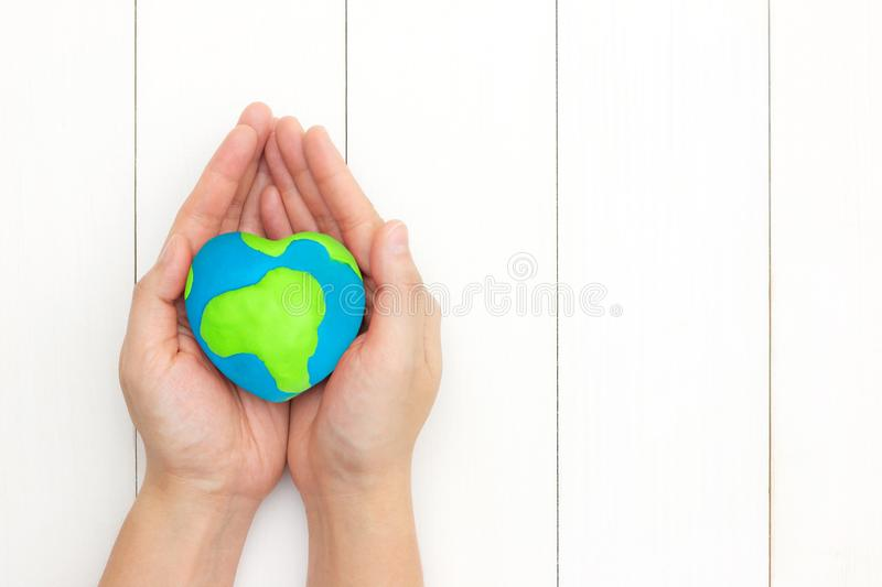 Happy mother earth day. Hands holding global heart shape over white wooden background with copy space. Happy mother earth day concept. Top view. Flat lay royalty free stock photos