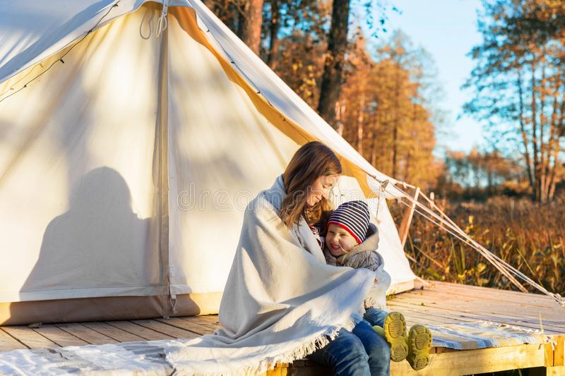 Happy mother embracing her kid with a blanket while sitting near canvas tent royalty free stock photos