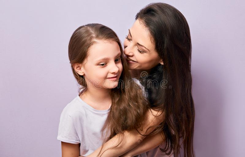 Happy mother and excited joying kid girl hugging with emotional smiling faces on purple background with empty copy space stock photo