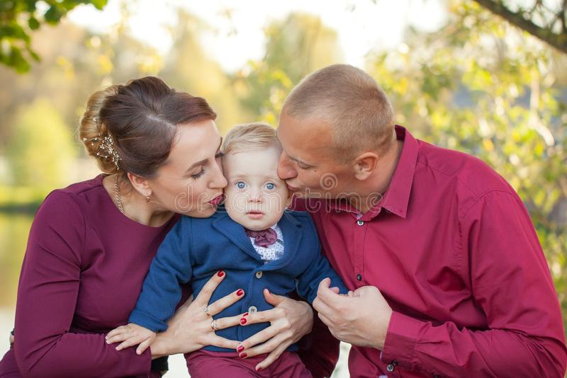 Happy mother and father kiss son in the park. Happiness in family life in summer day royalty free stock image