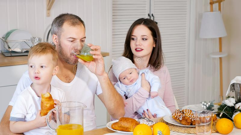 Happy mother, father and son having breakfast at home stock photos