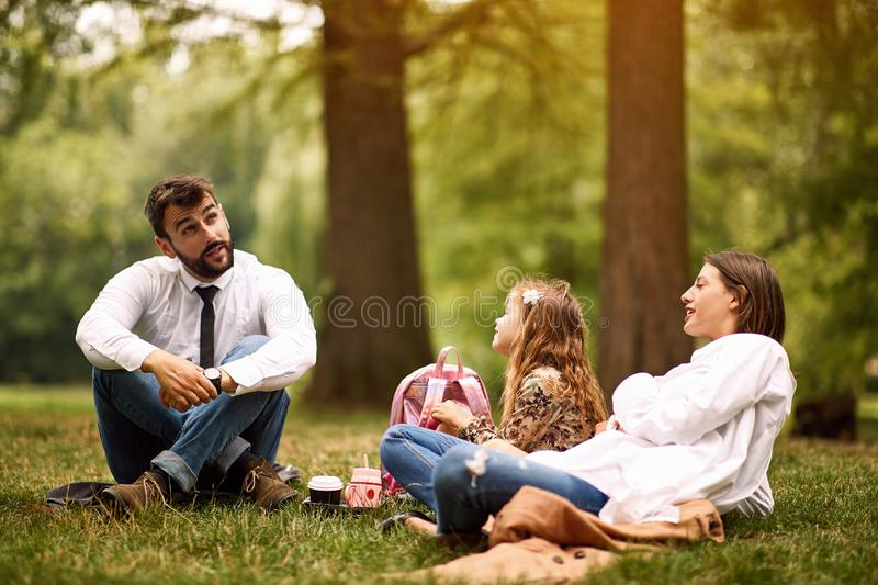 Mother and father with their daughter after work and school sitting and resting at park royalty free stock image
