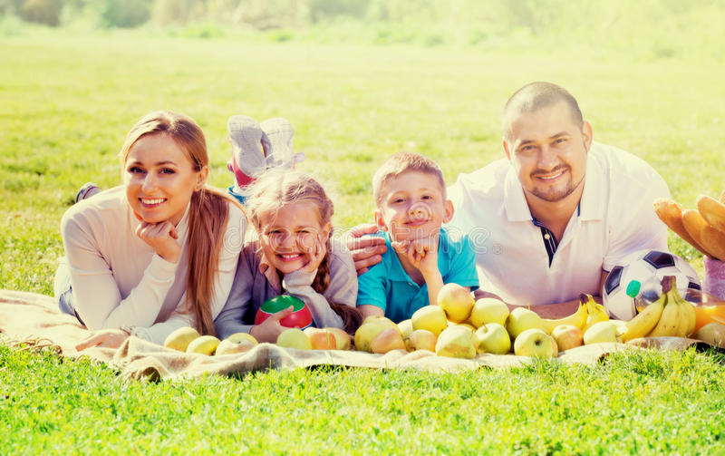 Happy mother and father with two teenagers lying in the garden stock images
