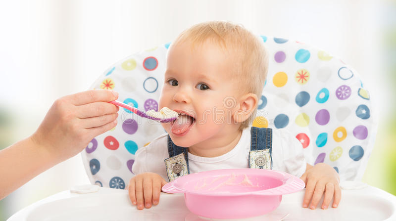Happy mother feeds funny baby from spoon stock photos