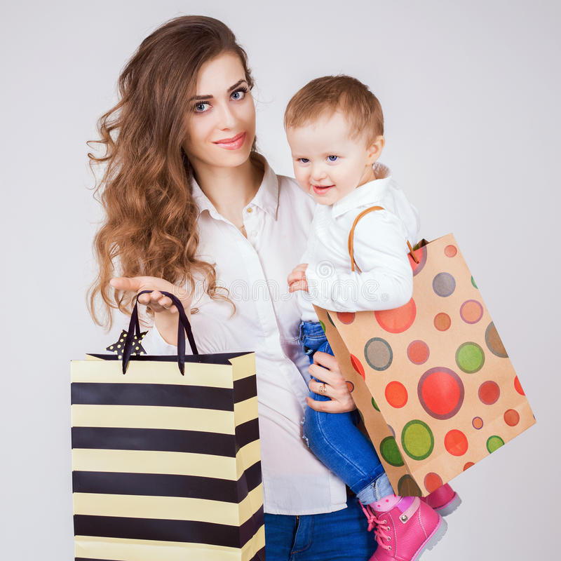 Happy mother and funny baby holding bags with purchases royalty free stock photo