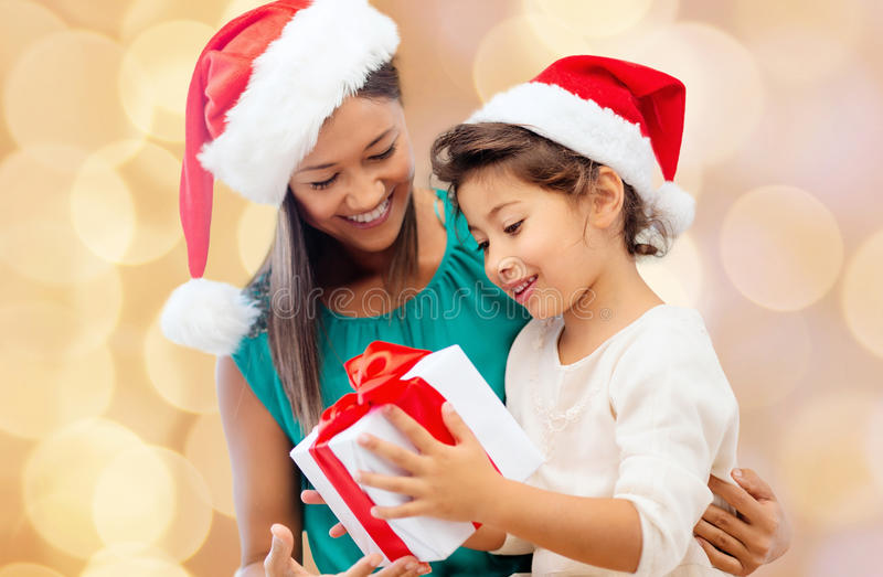 Happy mother and girl in santa hats with gift box. Christmas, holidays, celebration, family and people concept - happy mother and little girl in santa helper royalty free stock images