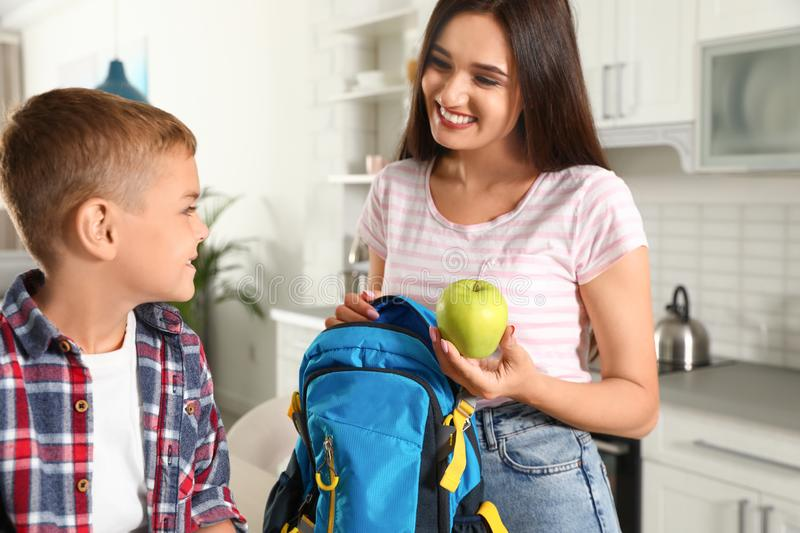 Happy mother giving apple to little child`s with school bag royalty free stock photos