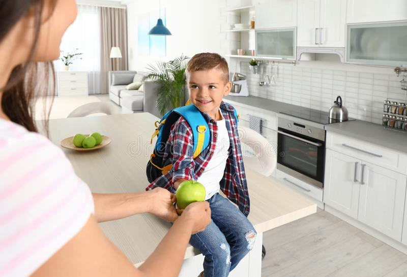 Happy mother giving apple to little child`s with school bag. In kitchen stock image