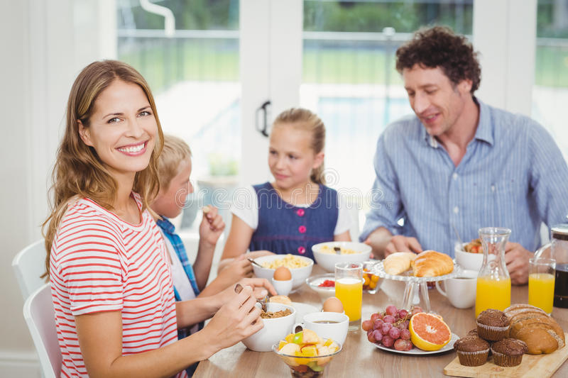 Happy mother having breakfast with family at table. Portrait of happy mother having breakfast with family at table in house royalty free stock photo