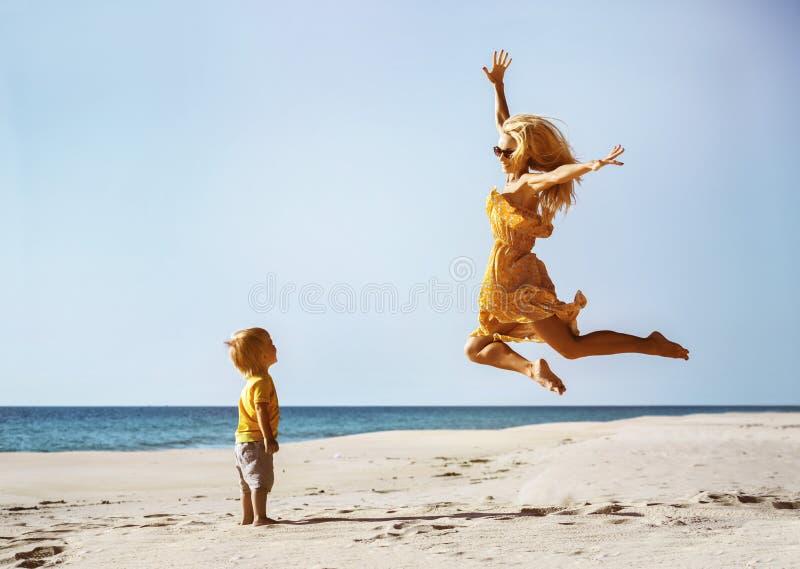 Happy mother having fun jump at beach royalty free stock photography
