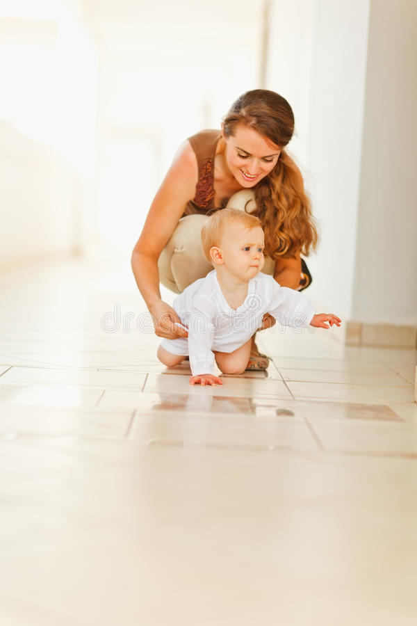 Happy Mother Helping Baby To Creep Stock Photography