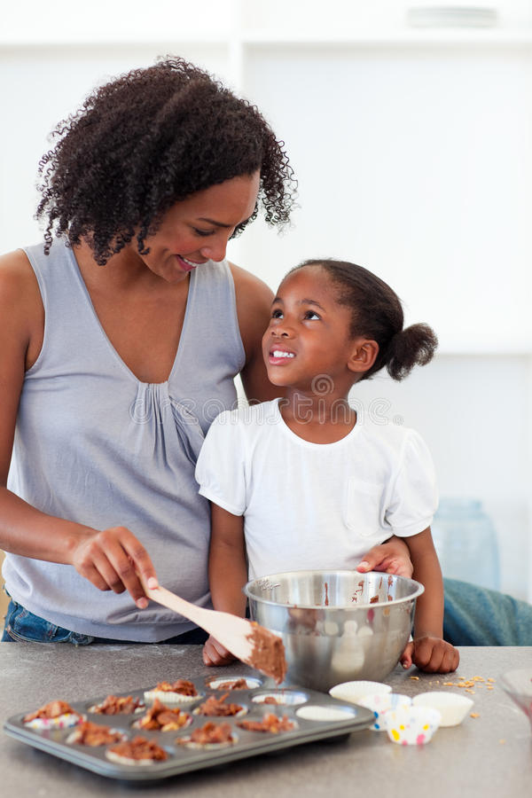 Happy mother helping her daughter cooking biscuits. In the kitchen royalty free stock photography