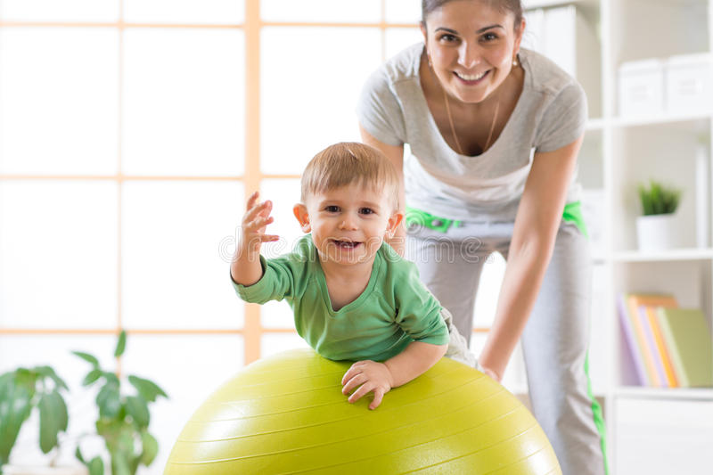 Happy mother and her baby on fitness ball. Gimnastics for kids on fitball. Happy mother and baby boy on fitness ball in nursery at home. Gimnastics for kids on royalty free stock image