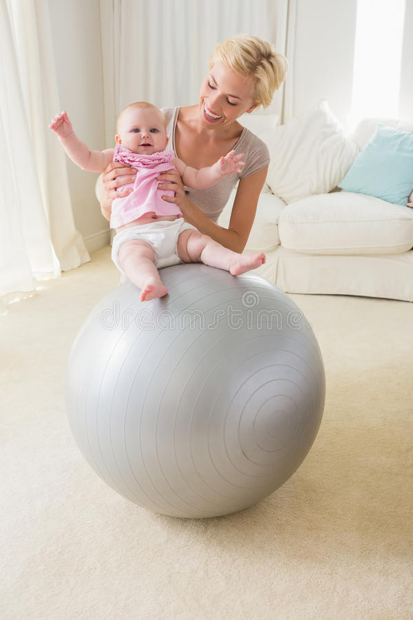 Happy mother with her baby girl in the exercice ball. At home in the living room royalty free stock photo