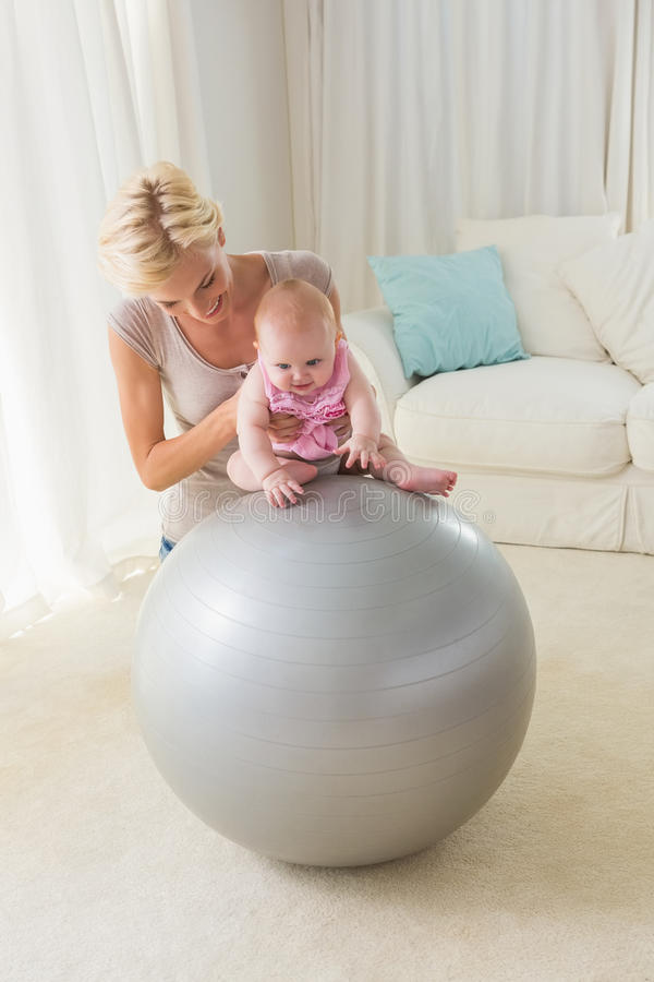Happy mother with her baby girl on the exercice ball. At home in the living room stock photography