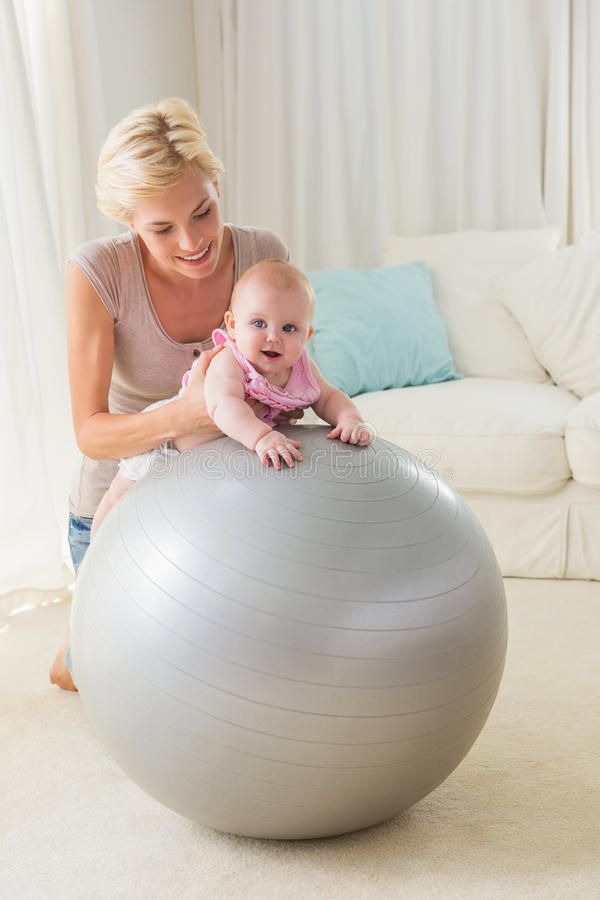 Happy mother with her baby girl in the exercice ball. At home in the living room royalty free stock image