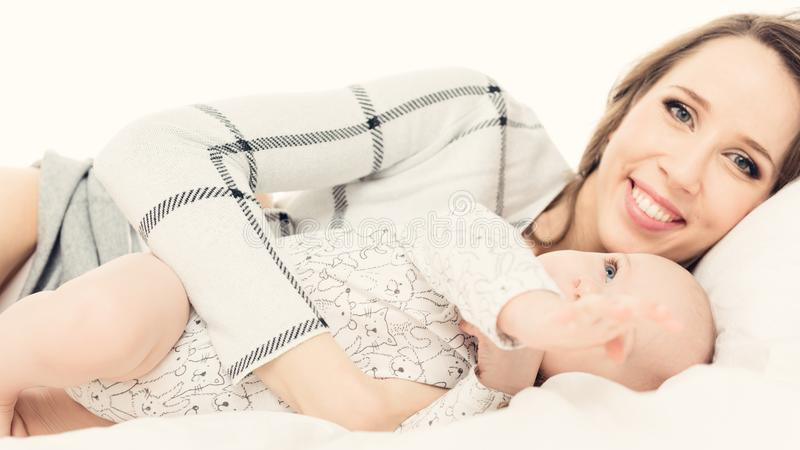 Happy mother and her baby son playing on a bed together. Happy family. Mother and newborn child. stock photos