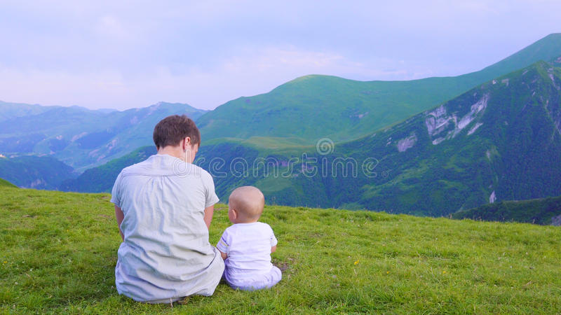 Happy mother and her child looking forward and pointing to sky. Family on trekking day in the mountains. Concrpt royalty free stock photography