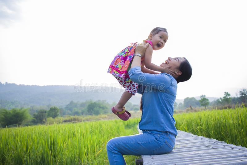 Happy Mother and her child play outdoors having fun, Green  rice field back ground. High resolution image gallery stock image
