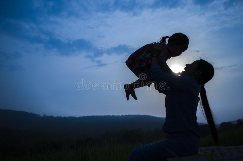 Happy Mother and her child play outdoors having fun, mother lifting daughter in rice field stock image