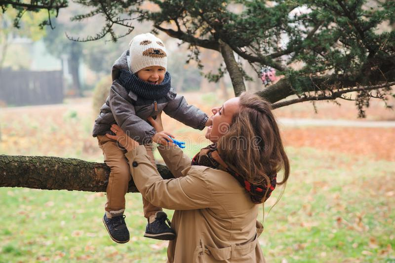 Happy mother and her child playing together in a autumn park. Happy autumn holidays. Autumn season, lifestyle stock image