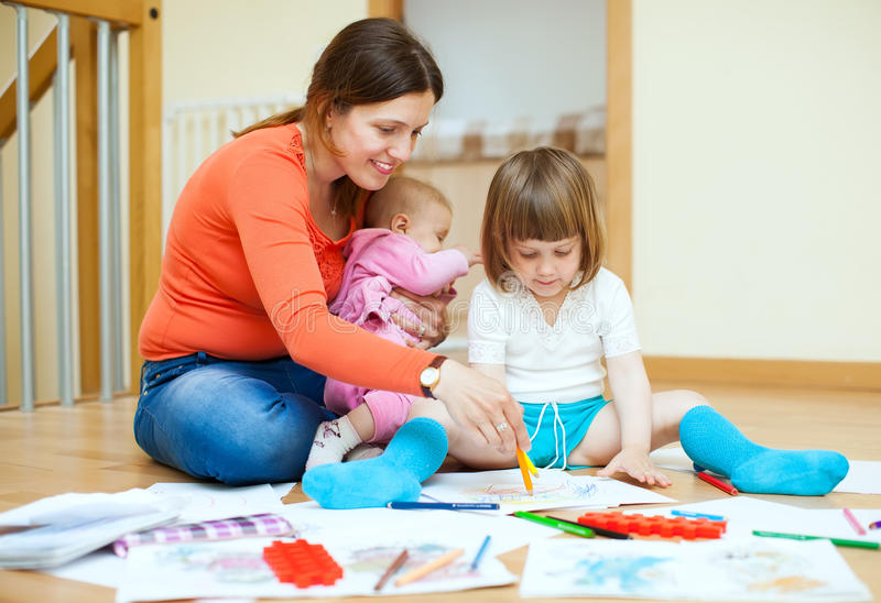 Happy mother and her children drawing on paper stock photos