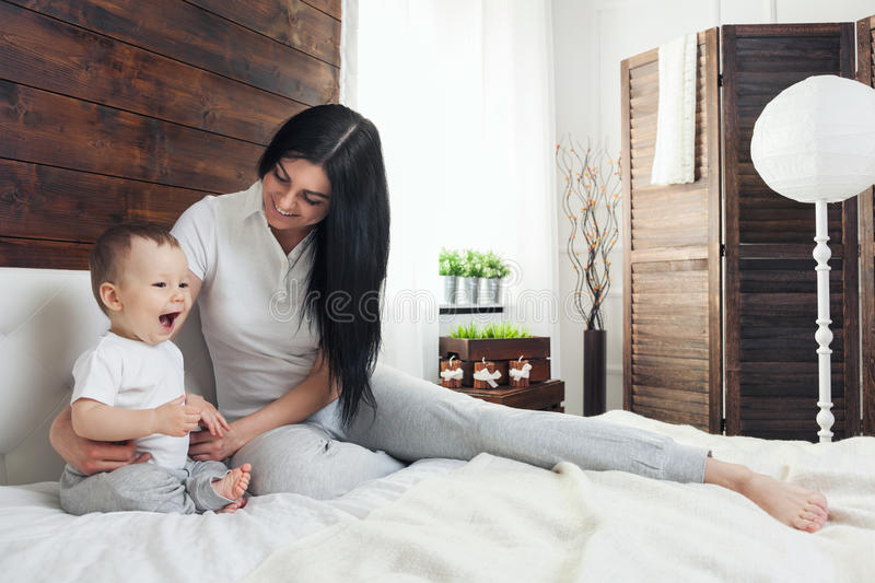 Happy mother with her cute child on the bed having a good time royalty free stock photos