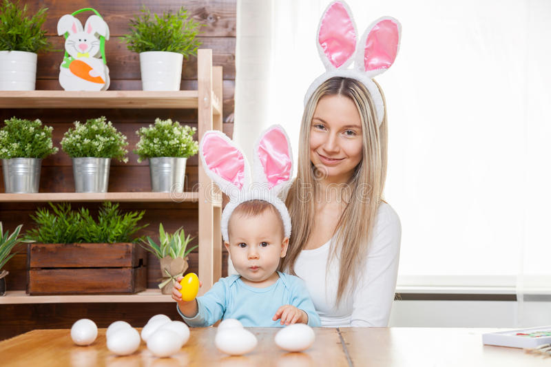 Happy mother and her cute child wearing bunny ears, getting ready for Easter. Easter concept. Happy mother and her cute child wearing bunny ears getting ready royalty free stock photos