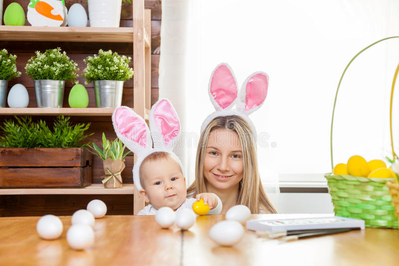 Happy mother and her cute child wearing bunny ears, getting ready for Easter. Easter concept. Happy mother and her cute child wearing bunny ears getting ready stock image