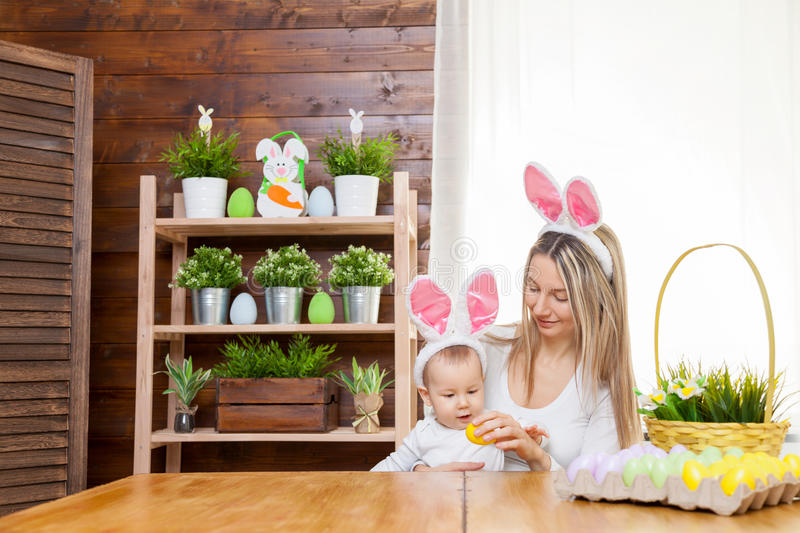 Happy mother and her cute child wearing bunny ears, getting ready for Easter. Easter concept. Happy mother and her cute child wearing bunny ears getting ready stock photography