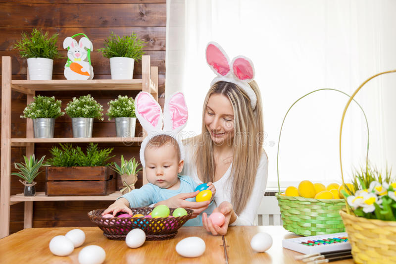 Happy mother and her cute child wearing bunny ears, getting ready for Easter. Easter concept. Happy mother and her cute child wearing bunny ears getting ready stock photos