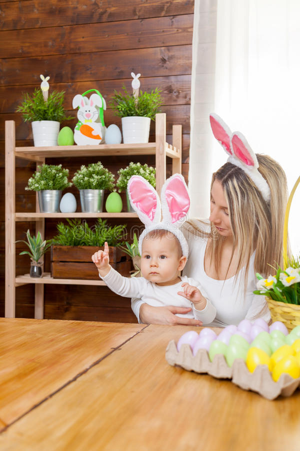 Happy mother and her cute child wearing bunny ears, getting ready for Easter. Easter concept. Happy mother and her cute child wearing bunny ears getting ready stock photo