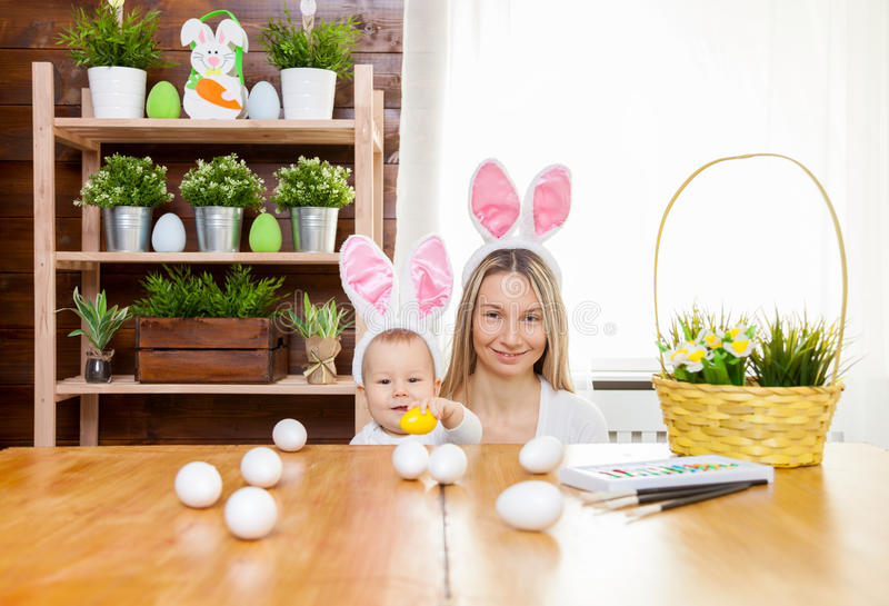 Happy mother and her cute child wearing bunny ears, getting ready for Easter. Easter concept. Happy mother and her cute child wearing bunny ears getting ready royalty free stock image