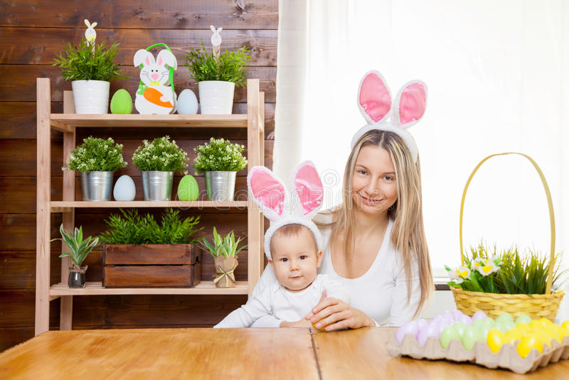Happy mother and her cute child wearing bunny ears, getting ready for Easter. Easter concept. Happy mother and her cute child wearing bunny ears getting ready royalty free stock photography
