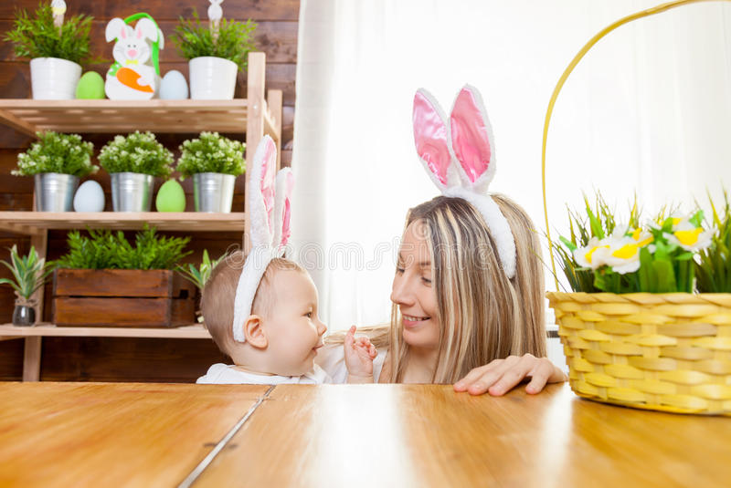 Happy mother and her cute child wearing bunny ears, getting ready for Easter. Easter concept. Happy mother and her cute child wearing bunny ears getting ready stock images