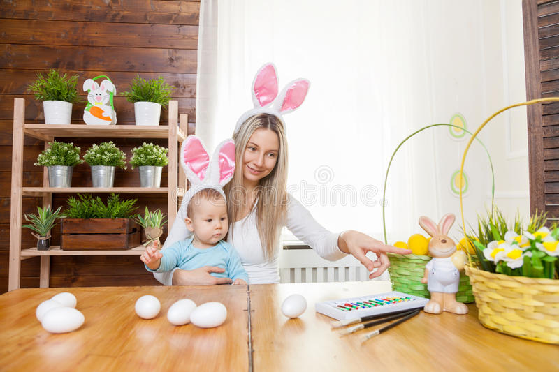 Happy mother and her cute child wearing bunny ears, getting ready for Easter. Easter concept. Happy mother and her cute child wearing bunny ears getting ready royalty free stock images