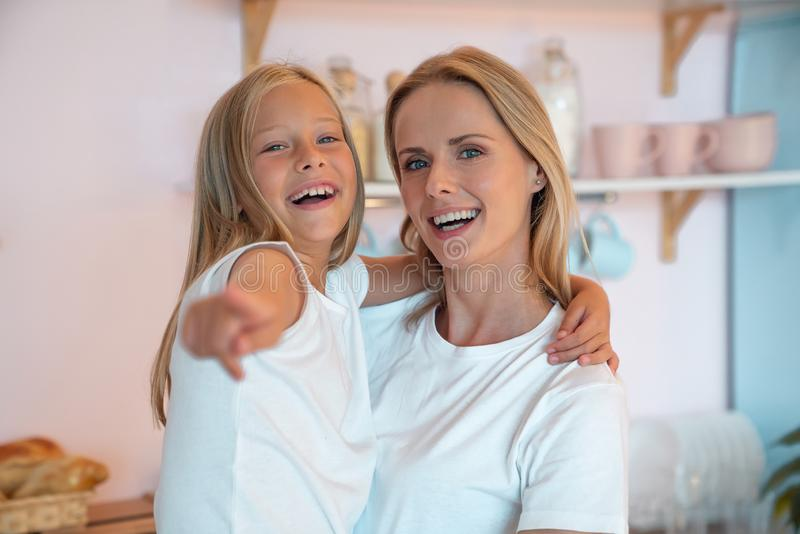 Happy mother and her cute little daughter are having fun at home smiling. Look there. girl is pointing at something interesting stock photos