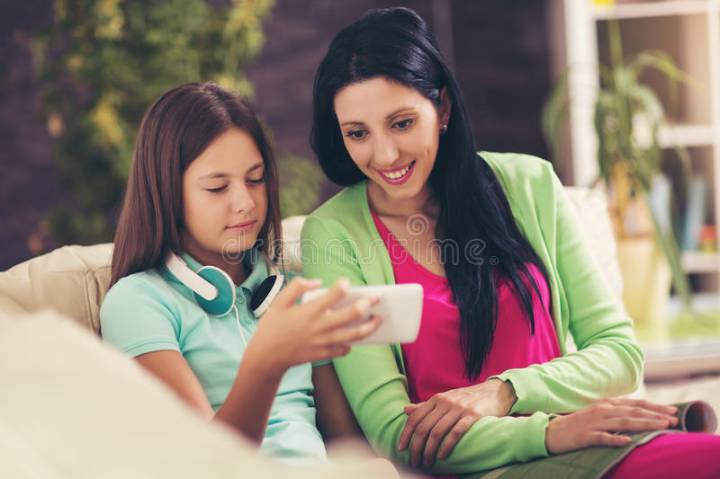 Happy mother and her cute teen daughter are looking at mobile phone stock photo