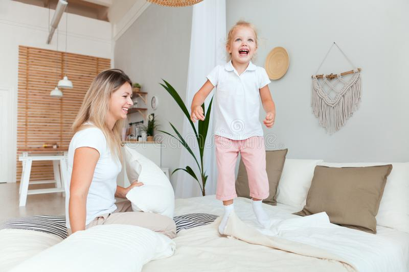 Happy mother and her daughter child girl playing and hugging in bedroom royalty free stock photos