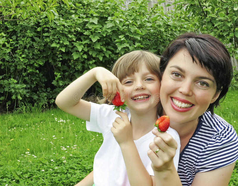Happy mother and her daughter eating strawberries royalty free stock photography