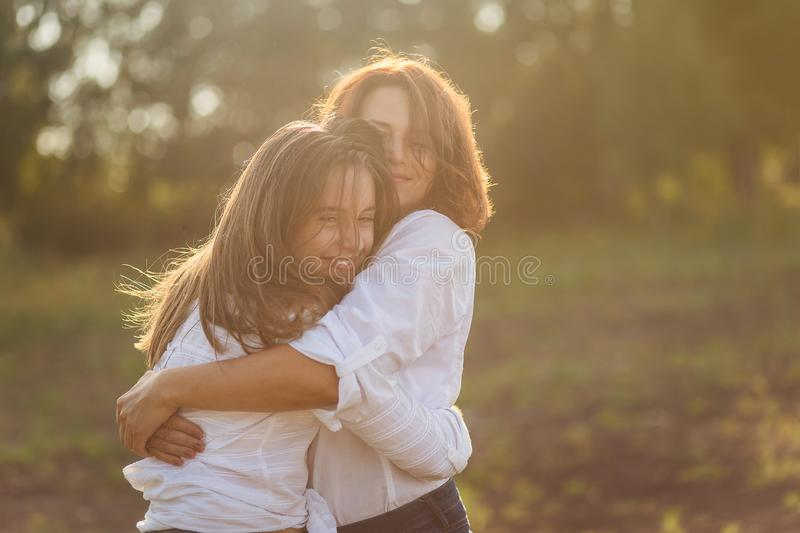 Happy mother with her daughter hugging a teenager in the summer royalty free stock photo
