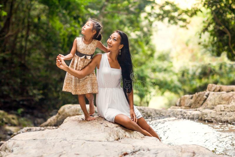 Happy mother with her daughter in the tropics near the waterfall stock photography