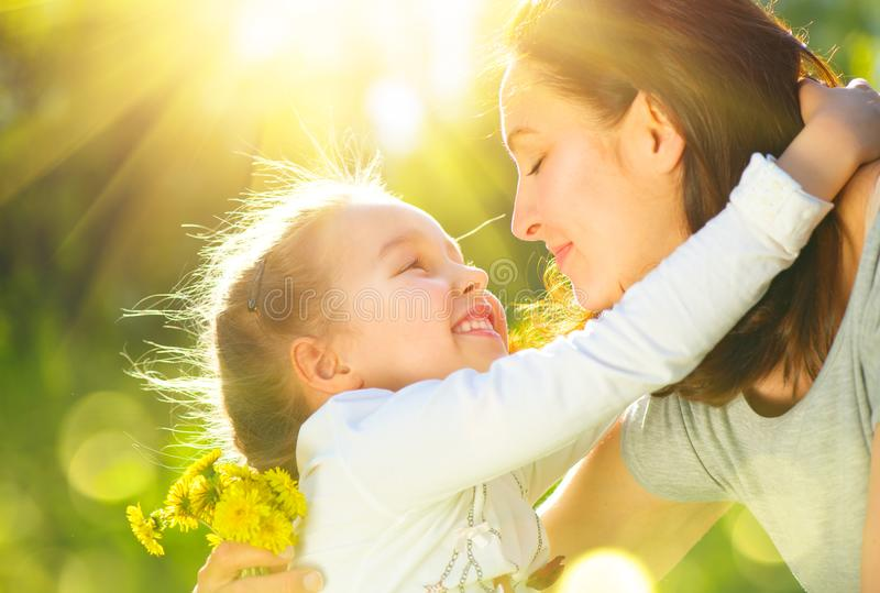 Happy mother and her little daughter outdoor. Mom and daughter enjoying nature together in green park. Mother`s Day concept royalty free stock photo