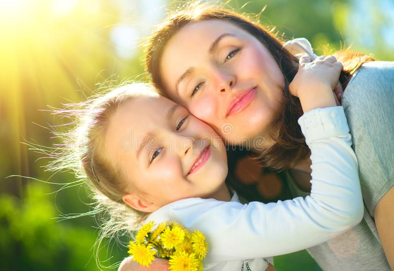 Happy mother and her little daughter outdoor. Mom and daughter enjoying nature together in green park. Mother`s Day concept stock image