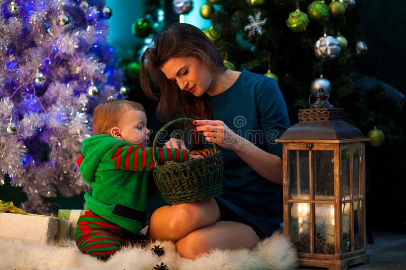 Happy mother with her little son look at Christmas gifts in wick. Happy mother with her little son sit on white fur rug and look at Christmas gifts in wicker stock image