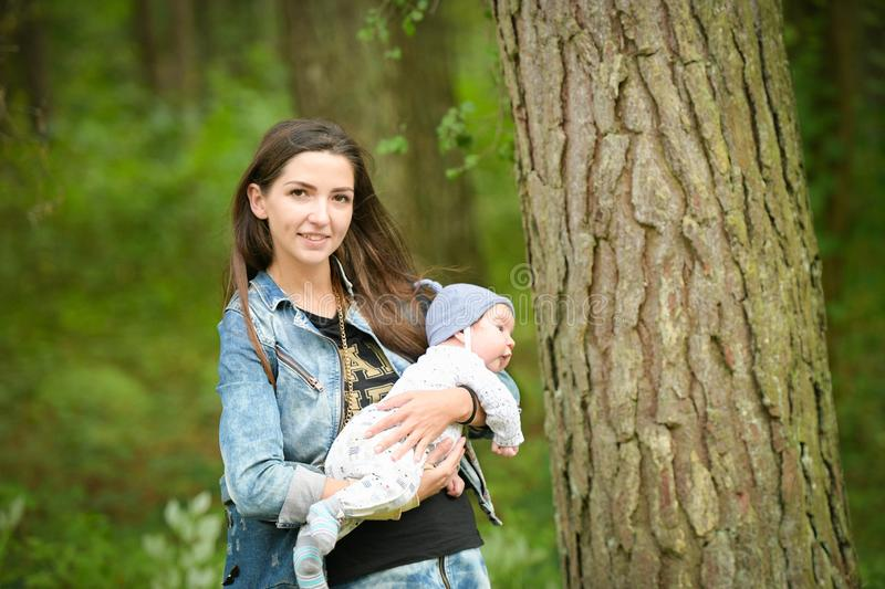 Happy mother with her newborn baby outdoors. young and stylish mother with long hair and a jeans jacket playing with her little stock photos