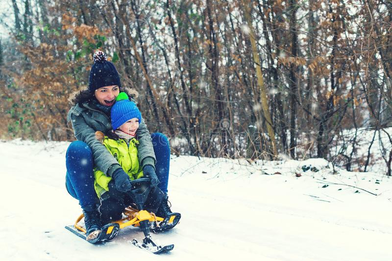 Happy mother and her son enjoying sleigh ride. Happy family with sled in winter having fun together. Child sledding. Family drivin royalty free stock photography