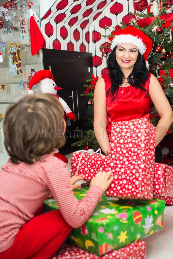 Happy mom and son with Christmas gifts. Happy mother and her son having conversation and preparing for Christmas stock photo