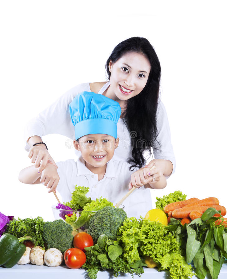 Happy mother and her son preparing a salad stock photos